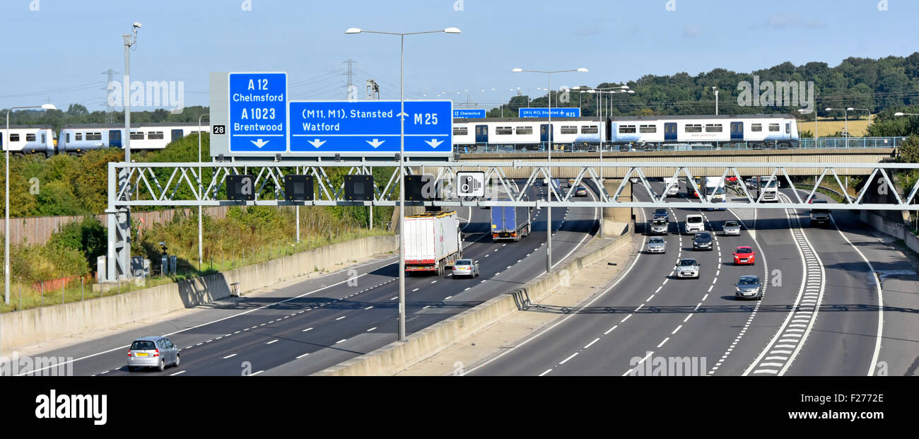 M25 motorway signs & railway bridge with Greater Anglia passenger train crossing above road traffic at junction - Stock Image
