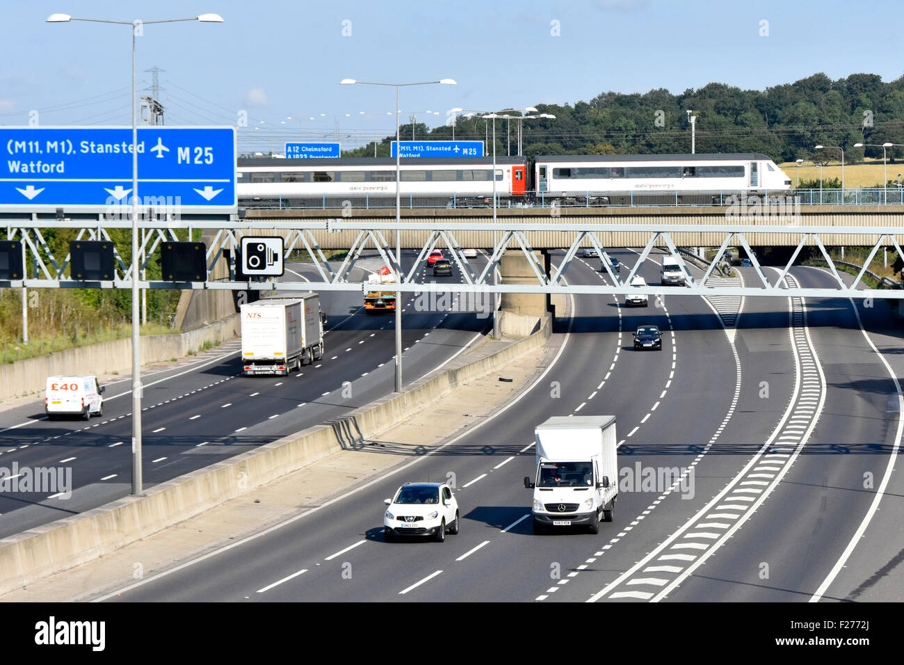 M25 motorway bridge and Greater Anglia inter city passenger train crossing above road traffic junction 28 at Brentwood - Stock Image