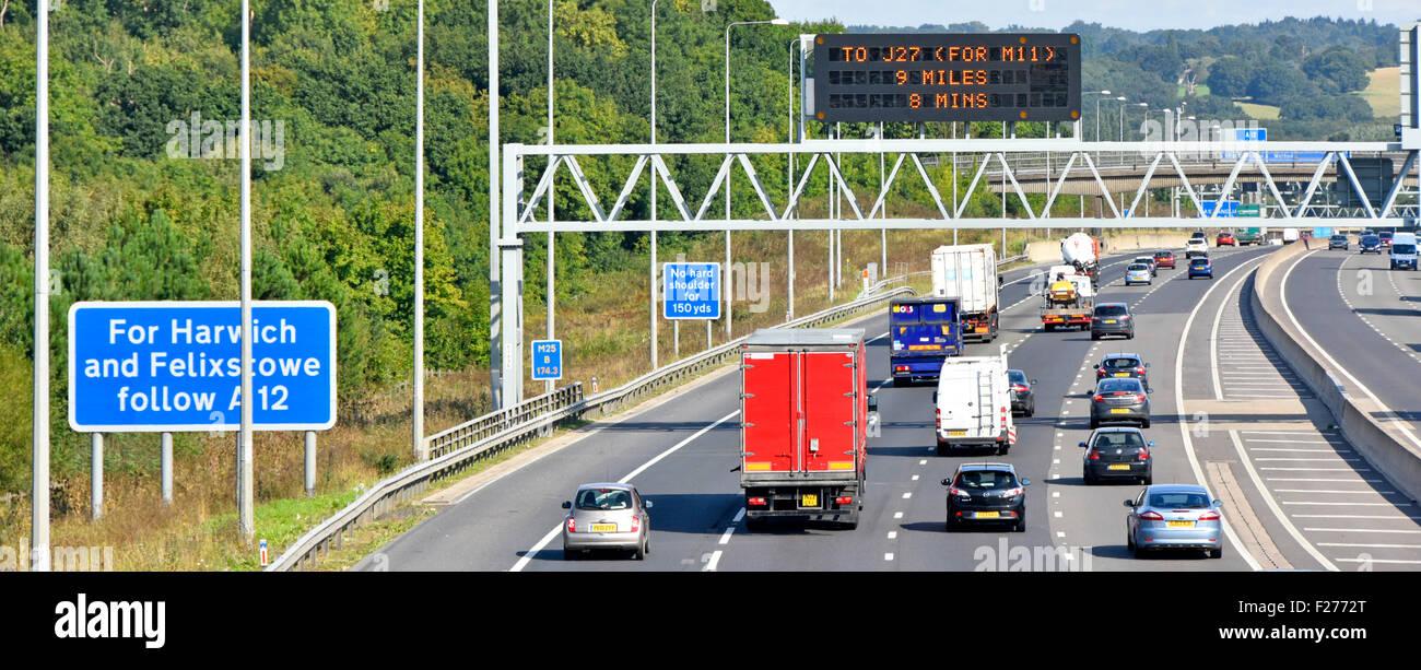 M25 motorway four lane gantry mounted electronic information sign conventional blue roadside signs beside hard shoulder - Stock Image