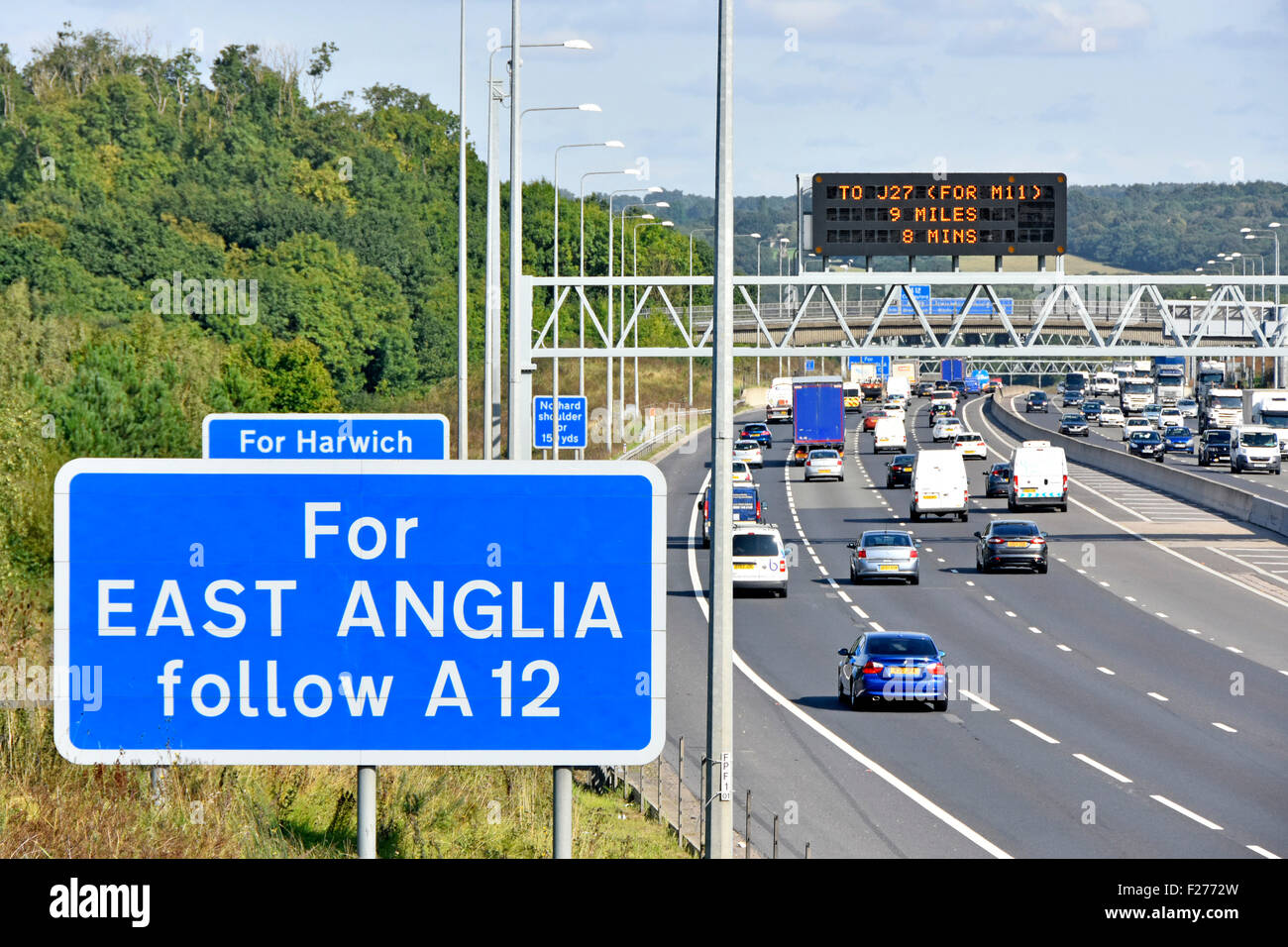 M25 motorway gantry mounted electronic information sign with conventional blue roadside signs for East Anglia route - Stock Image