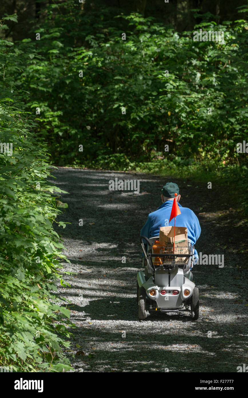 Man in motorized wheelchair on a trail in Sitka National Historic Park, Sitka, Alaska. - Stock Image