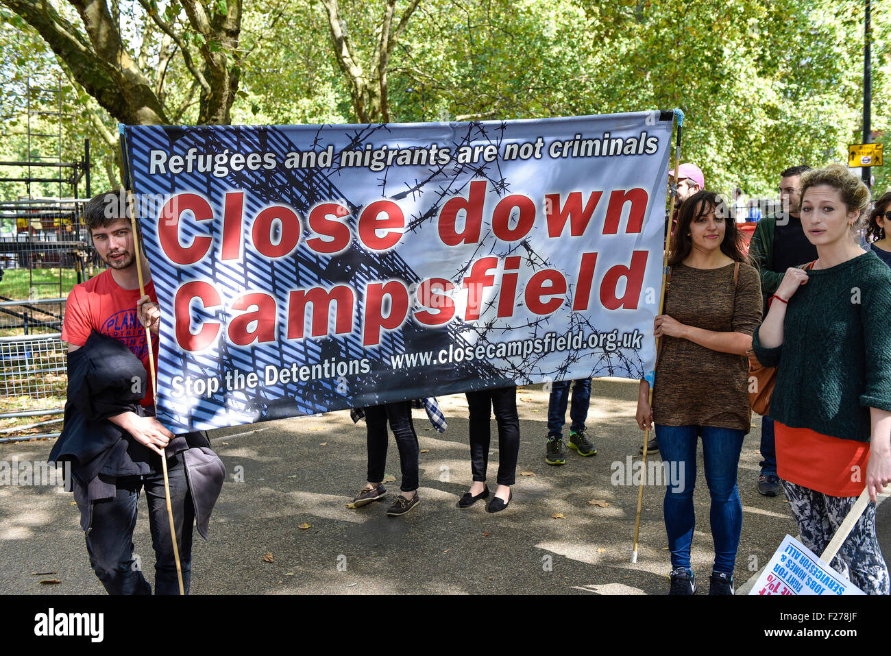 A demonstrators holding a banner demanding the closure of Campsfield Detention Centre. - Stock Image