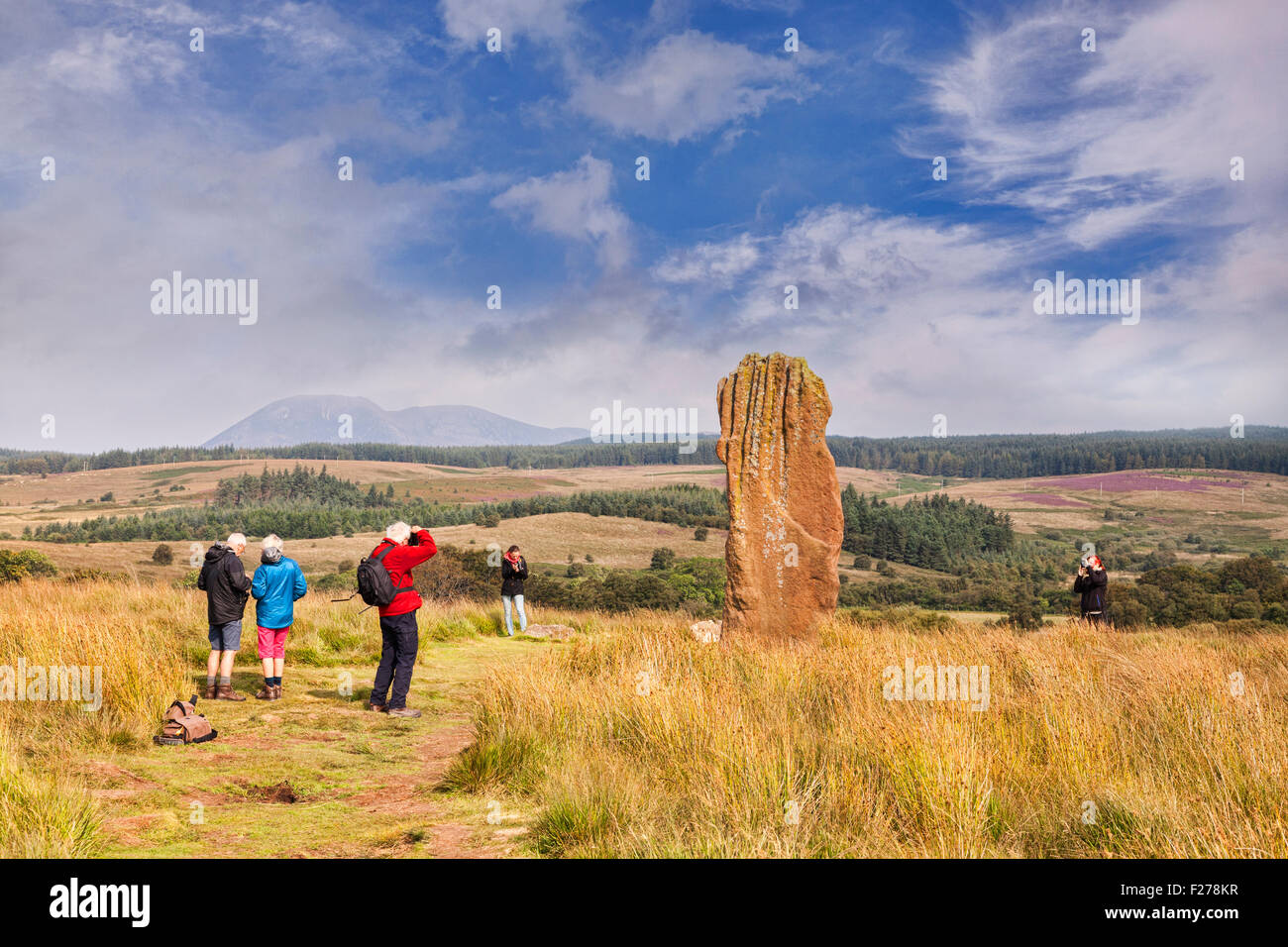 Tourists taking photos of one of the standing stones on Machrie Moor, Arran, North Ayrshire, Scotland. - Stock Image