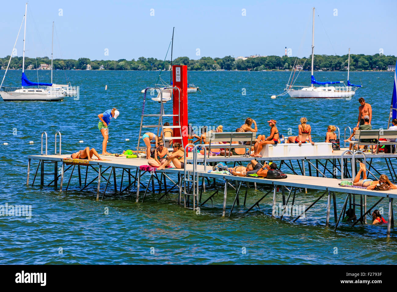 People enjoying the summer in Madison Wisconsin at the Memorial Union pier on Lake Mendota - Stock Image