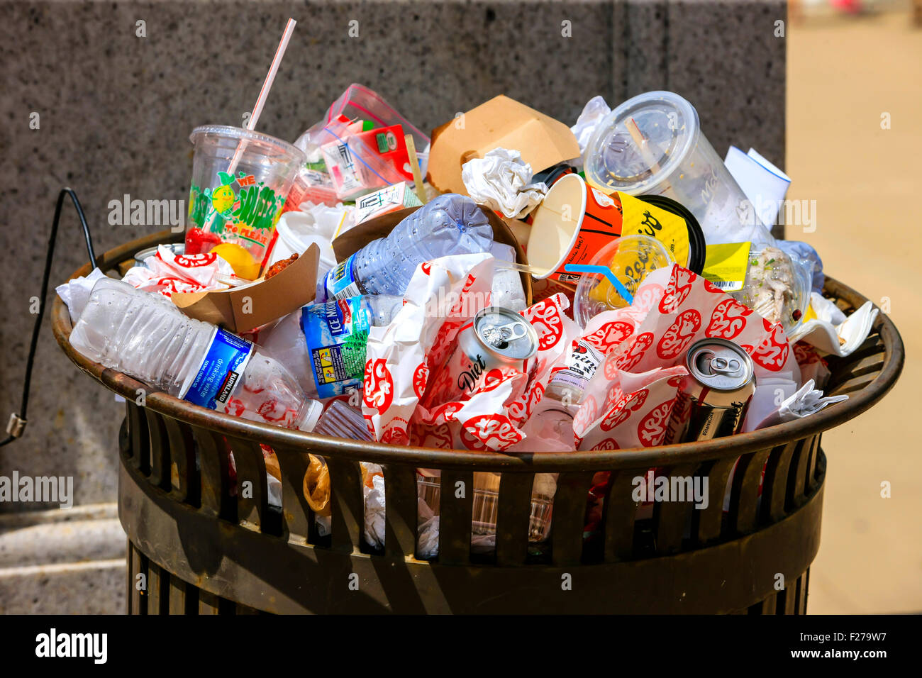 A trash can overflowing with empty drinks containers and food wrappers - Stock Image