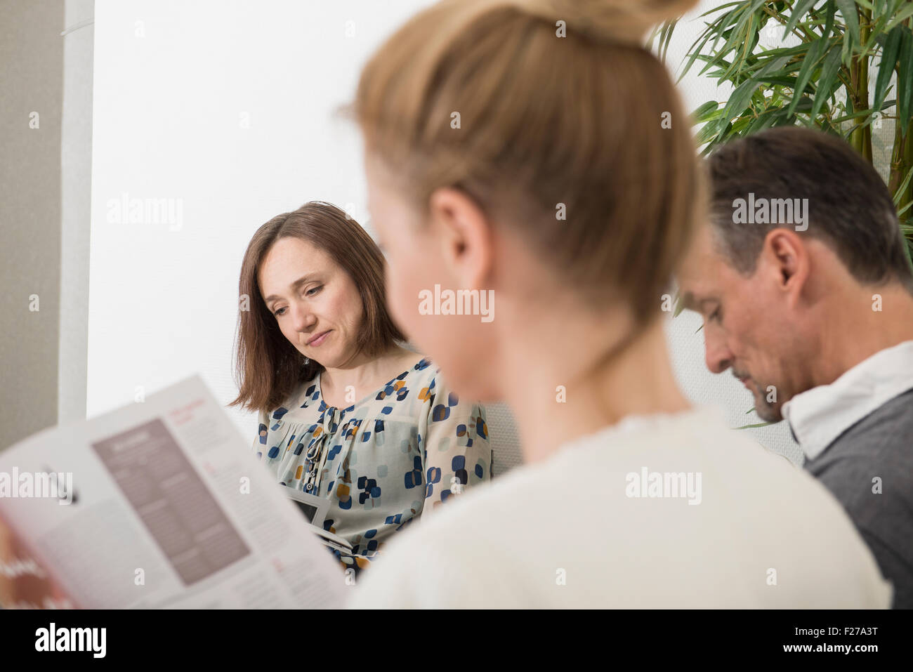 Three people sitting in waiting area of hospital, Munich, Bavaria, Germany - Stock Image