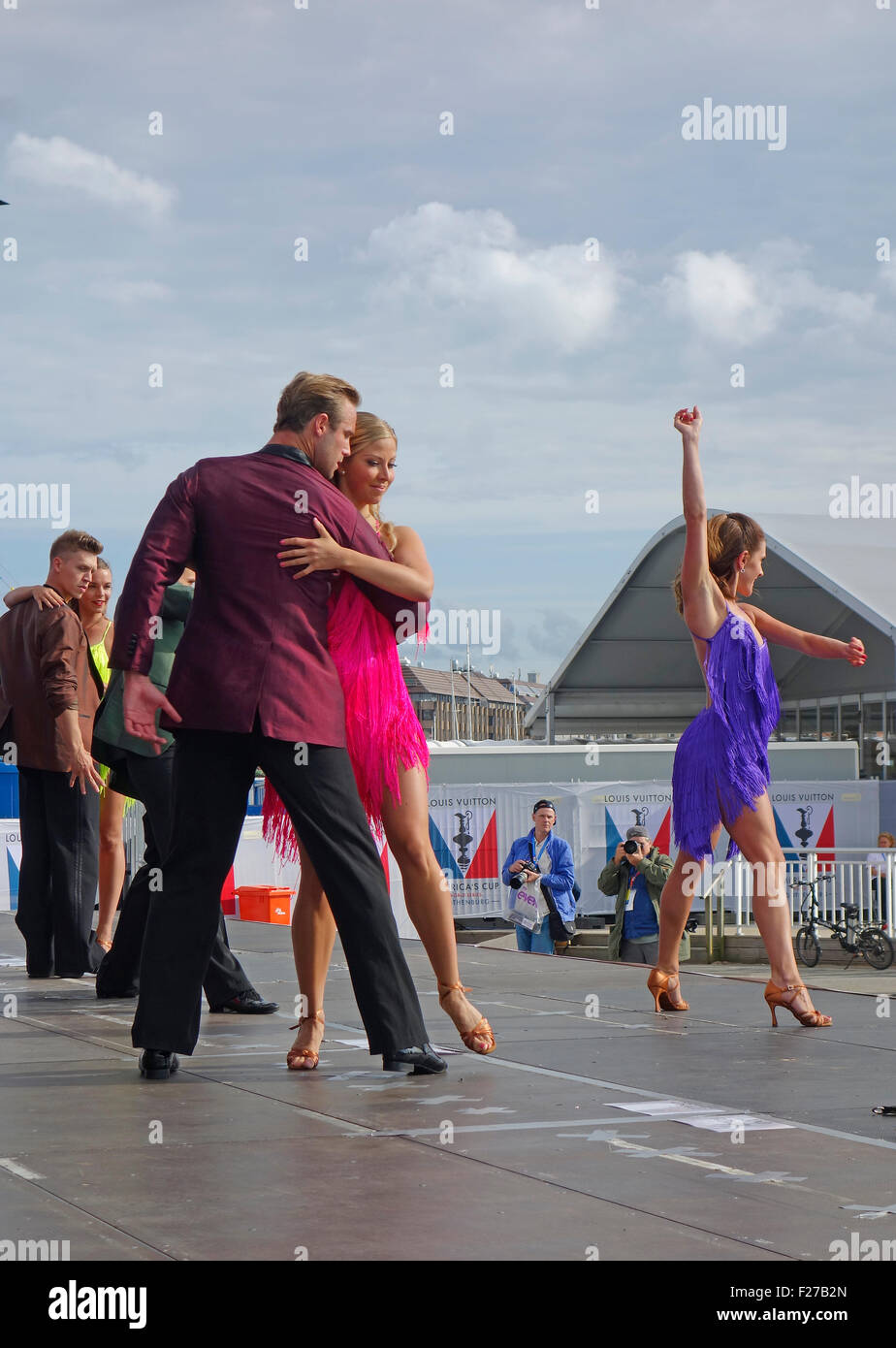 Dancing couples perform on stage. - Stock Image
