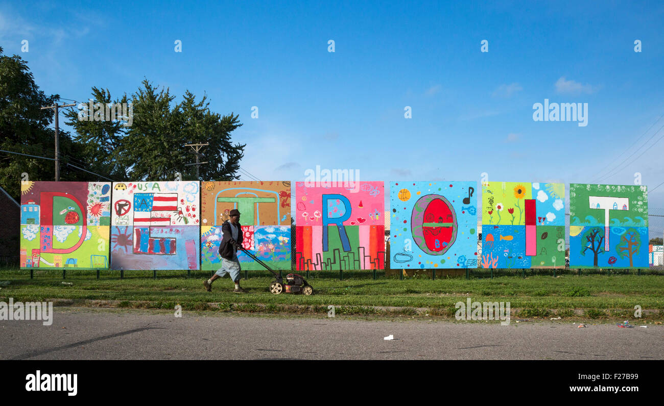 Detroit, Michigan - A man mows the grass in front of a painting spelling out 'Detroit' on the city's - Stock Image