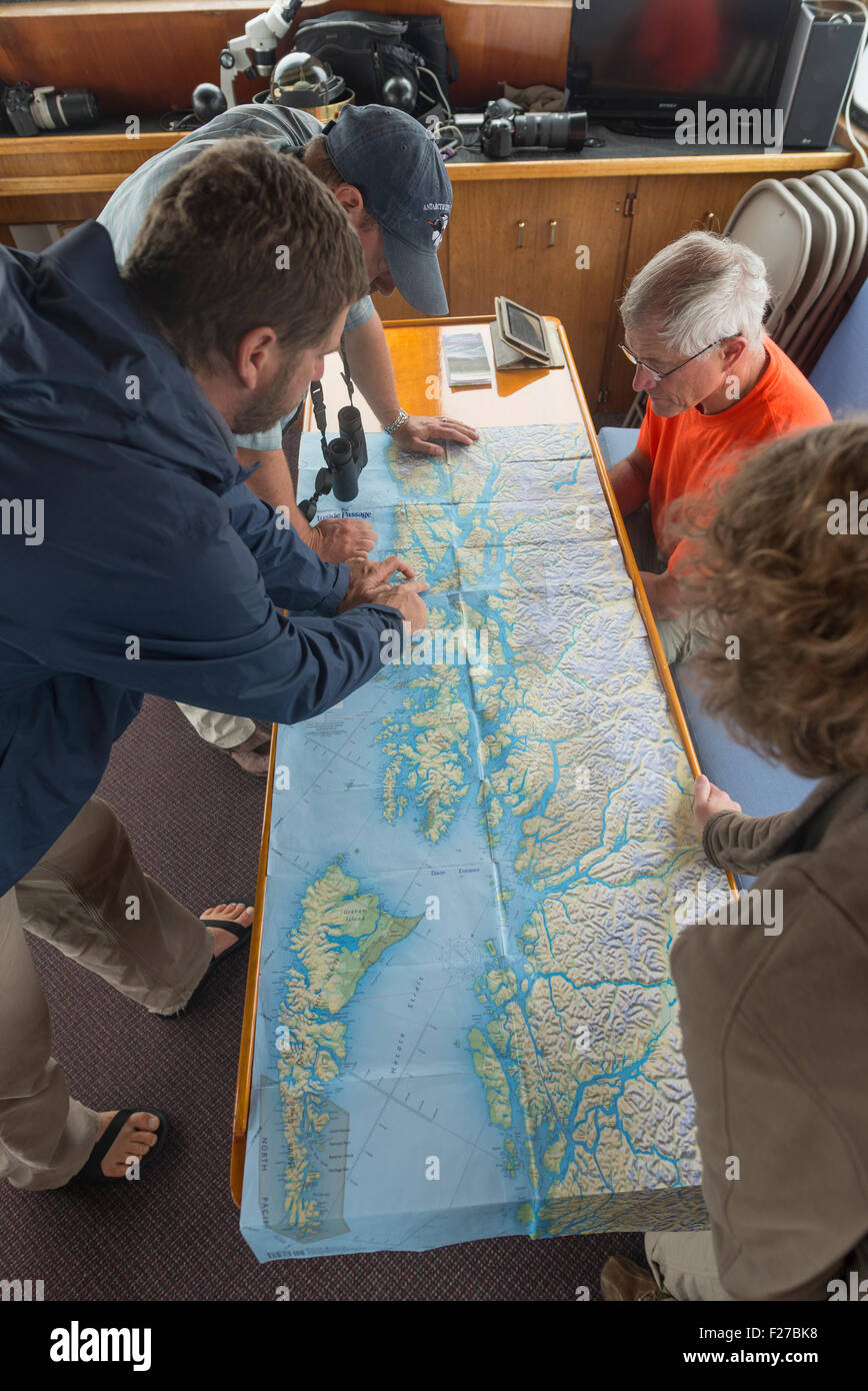 Group looking at a map on a small cruise ship in Alaska. - Stock Image