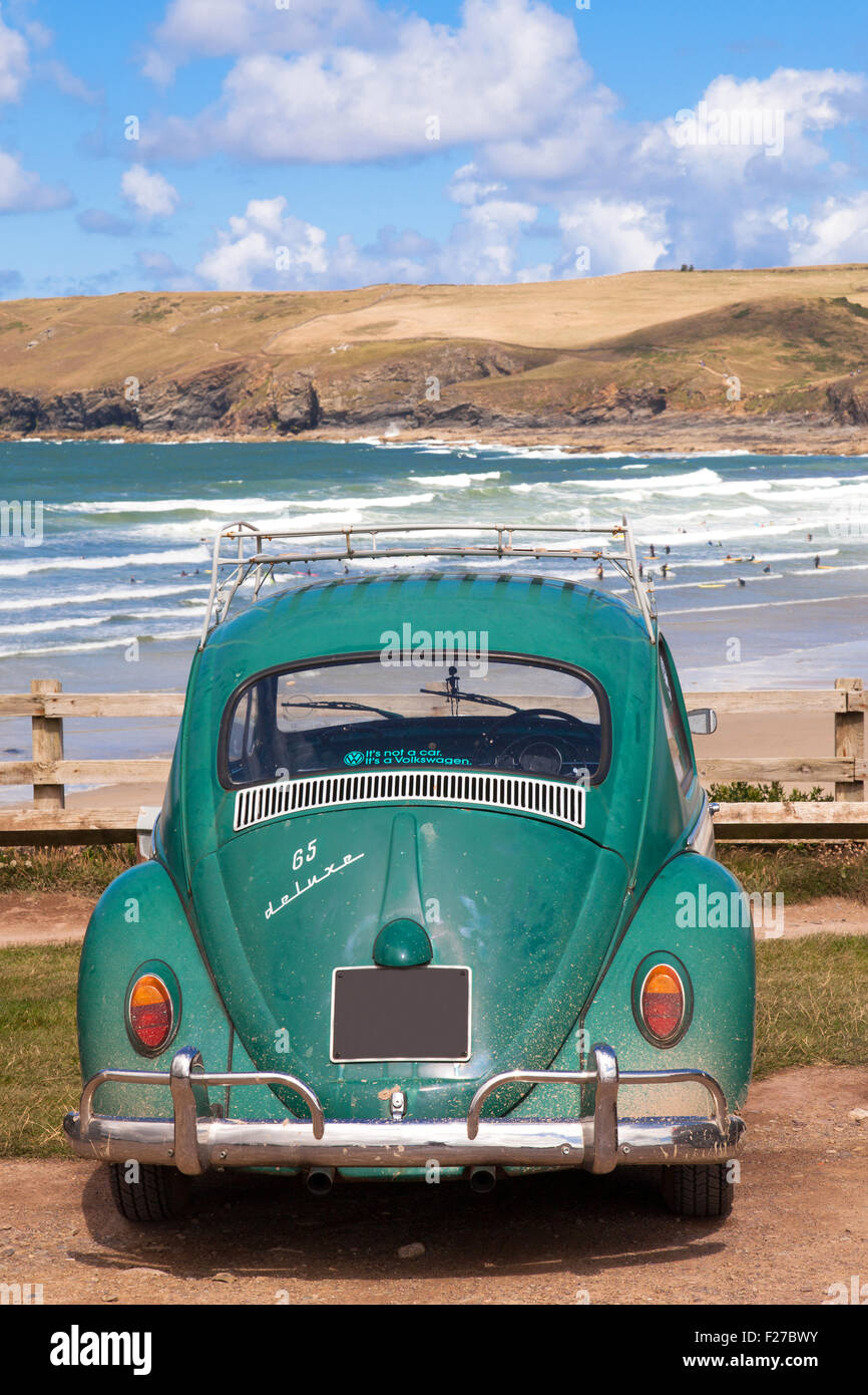 A classic 1960's VW Beetle car overlooking the beach at Polzeath, Cornwall, England, U.K. - Stock Image
