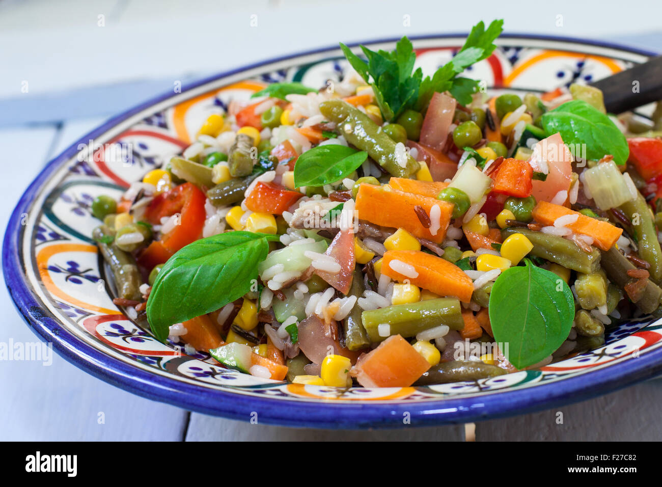 fresh rice salad with vegetables on decorated bowl - Stock Image