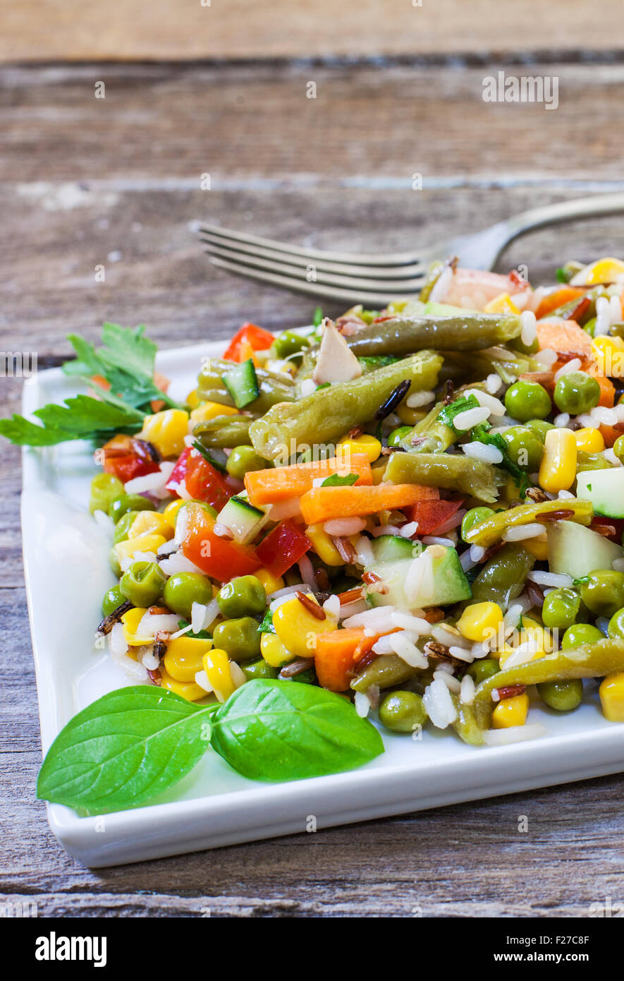 fresh rice salad with vegetables on white tray - Stock Image
