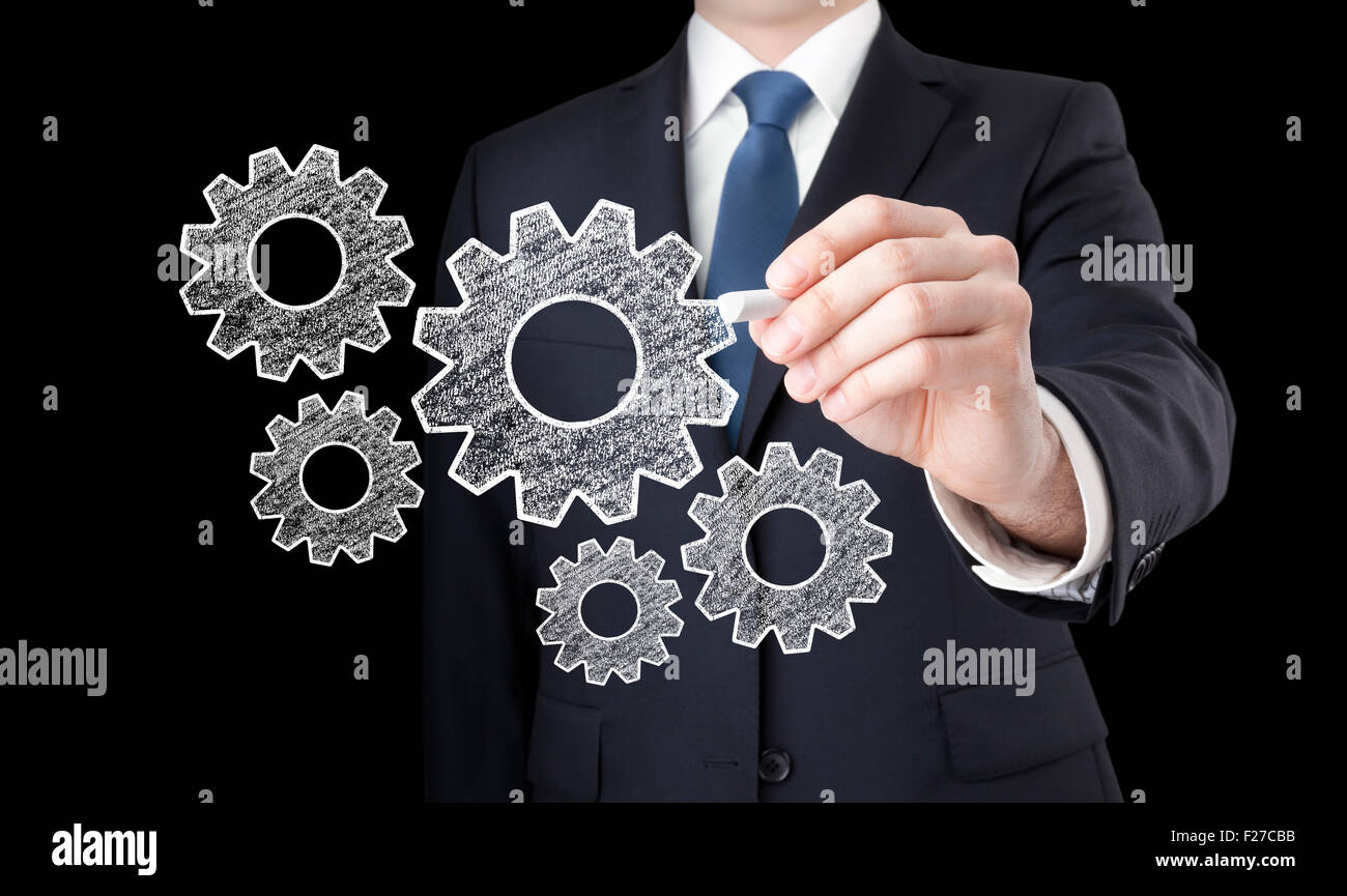 Businessman drawing gears with chalk - Stock Image