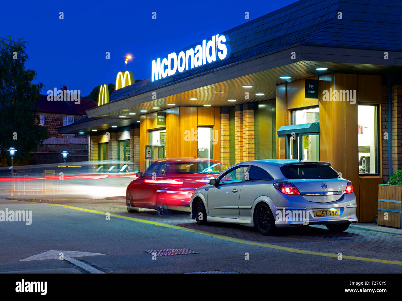 Cars at McDonald's drive-in restaurant, at night, England UK - Stock Image