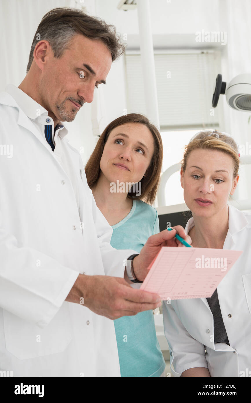 Dentists discussing the index card of a patient with dental assistant, Munich, Bavaria, Germany - Stock Image