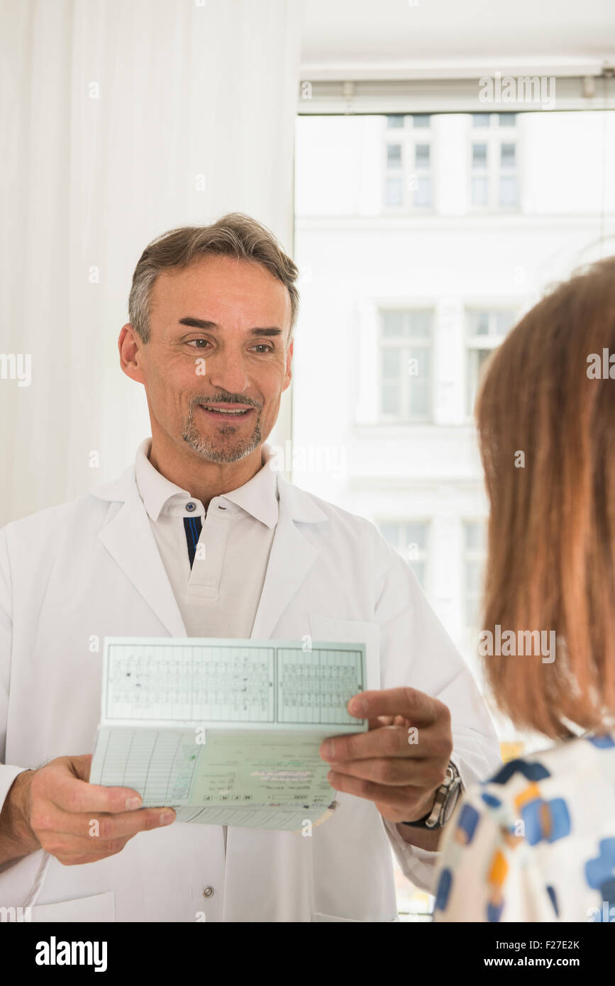 Doctor holding medical record and talking to patient in hospital, Munich, Bavaria, Germany - Stock Image