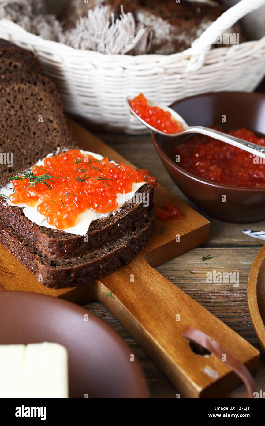 Bread with butter and caviar on a cutting board, food - Stock Image
