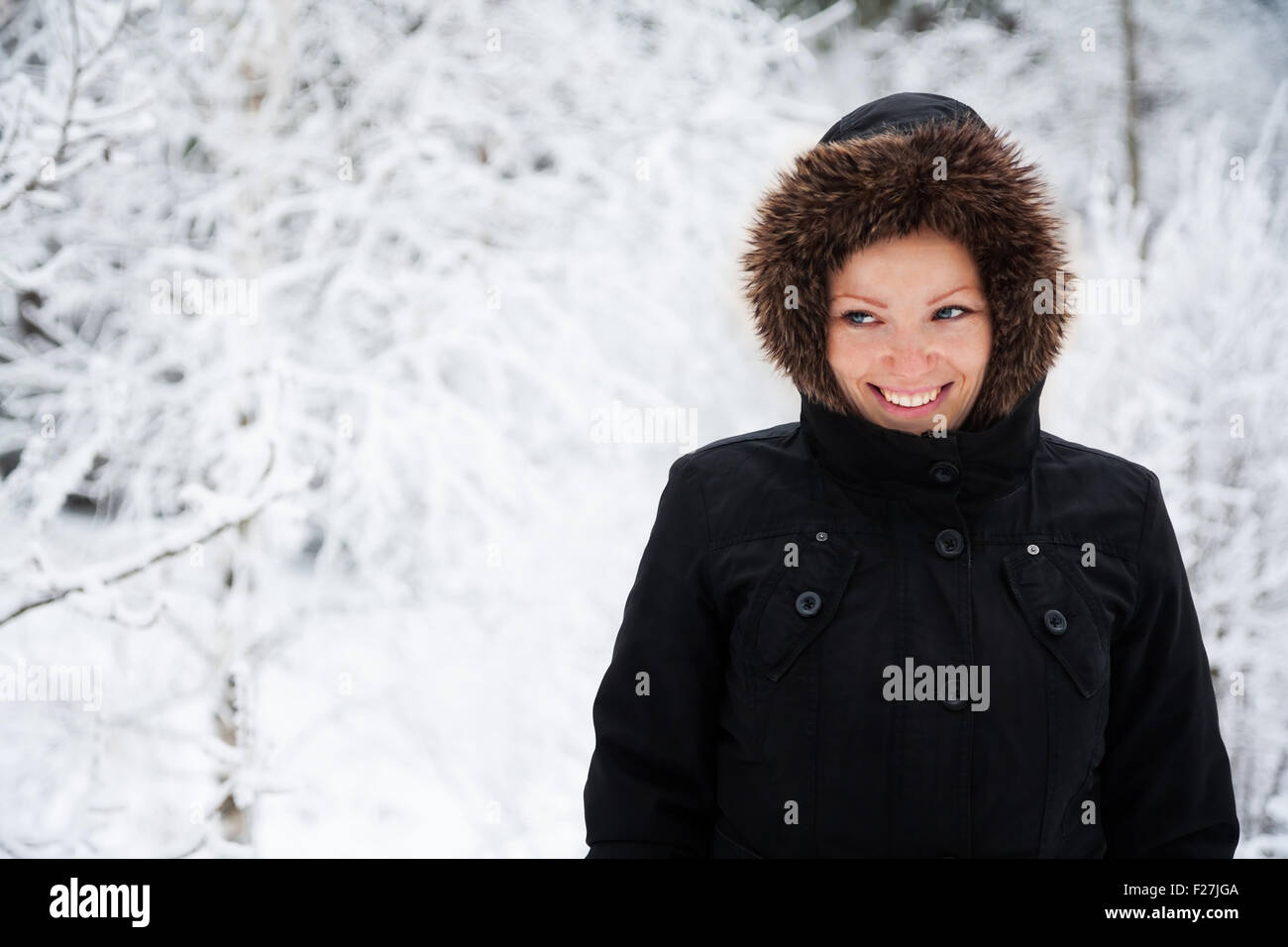 Cheerful Caucasian Young Woman in Snowy Weather in park with snow-covered trees, Copy Space - Stock Image