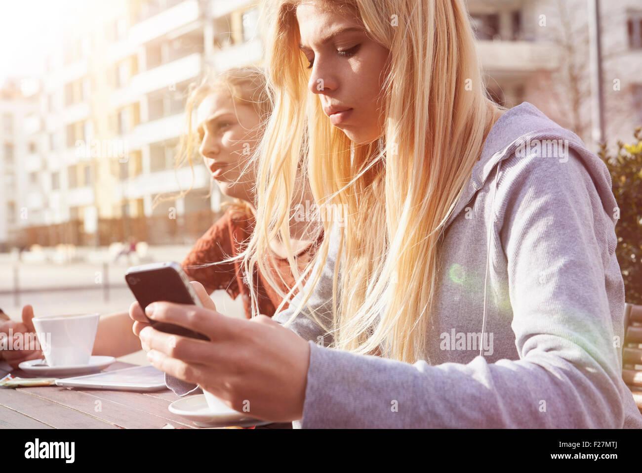 Teenage girl text messaging at sidewalk cafe, Munich, Bavaria, German - Stock Image