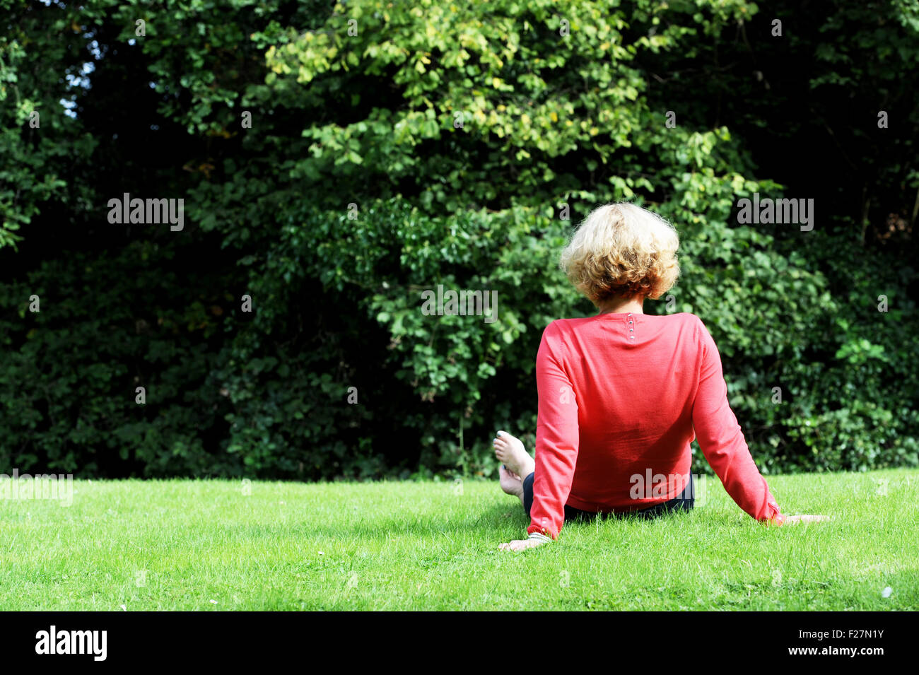 Back view of middle aged woman wearing coral pink coloured top and blue trousers sitting on grass outdoors Stock Photo