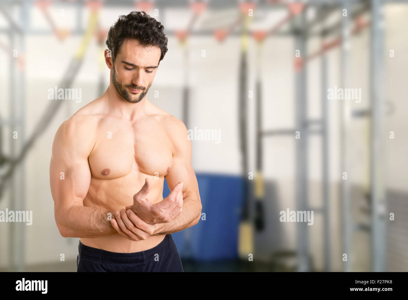 Male with pain in his wrist, isolated in a gym - Stock Image
