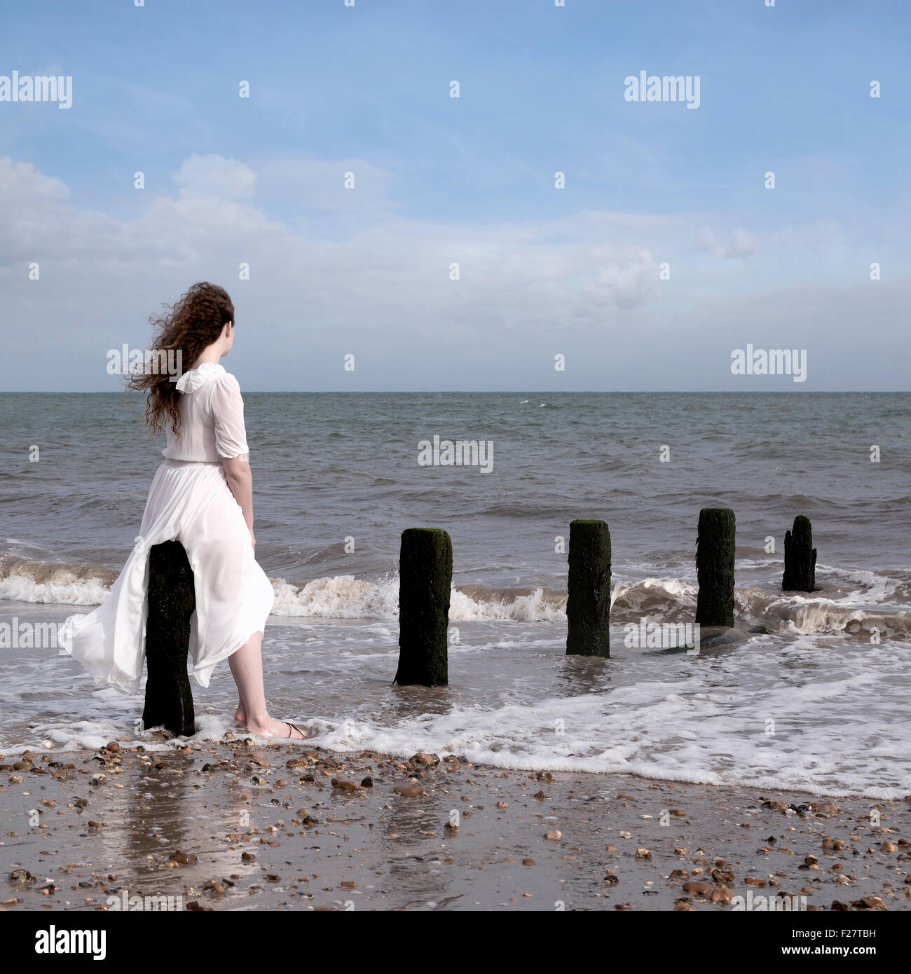 a woman in a white dress is sitting on a wooden pole in the sea - Stock Image