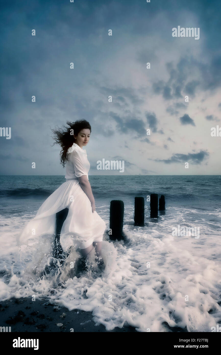 a woman in a white dress is sitting on a wooden pole in the sea Stock Photo