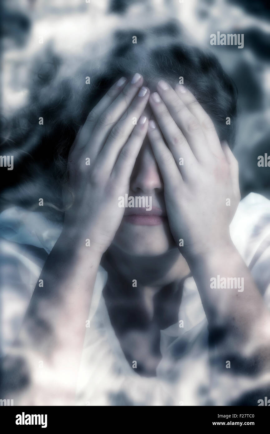 a woman in distress, hiding behind her hands - Stock Image