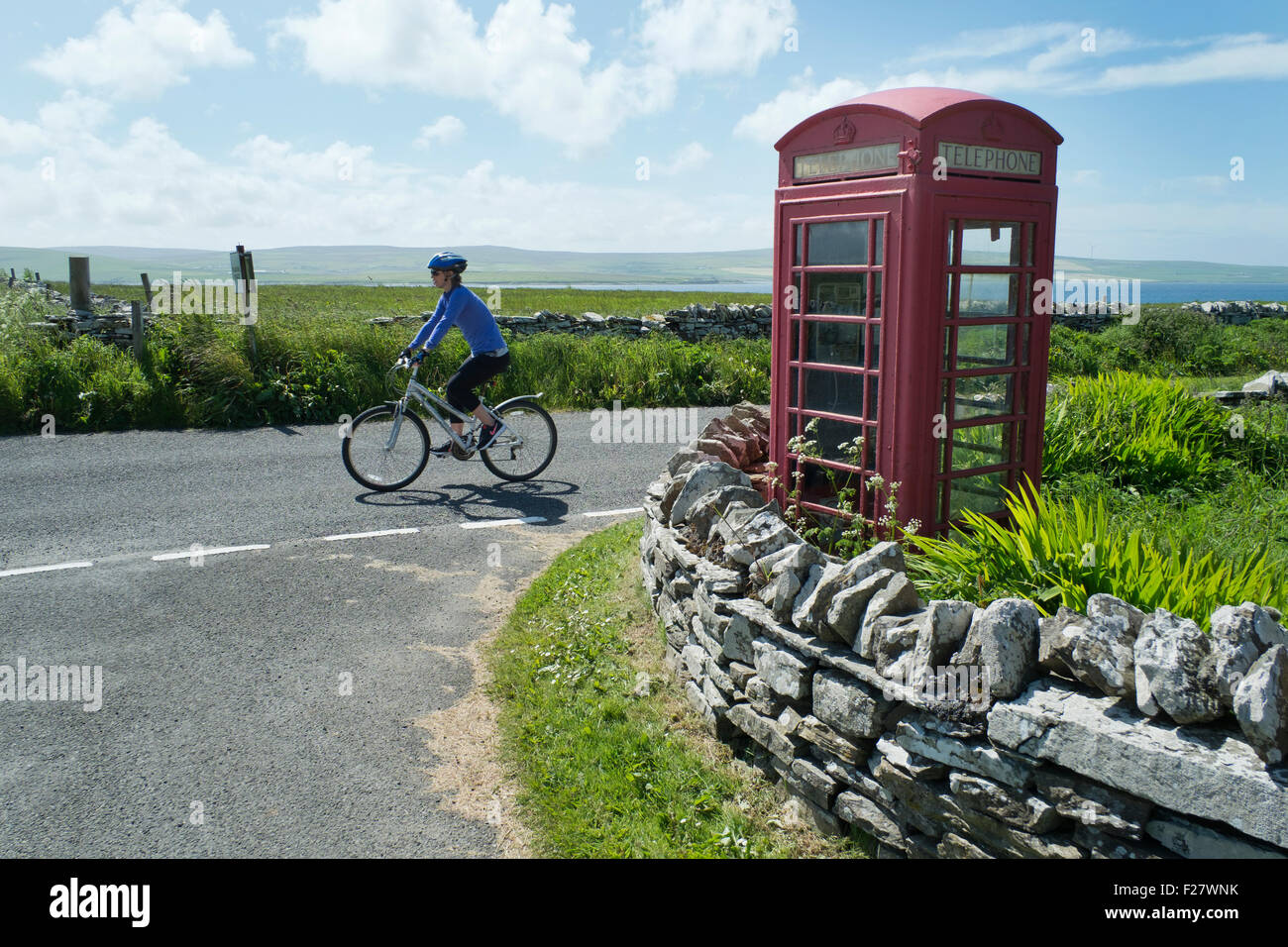 Cyclist and Telephone box, Rousay, Orkney, Scotland - Stock Image