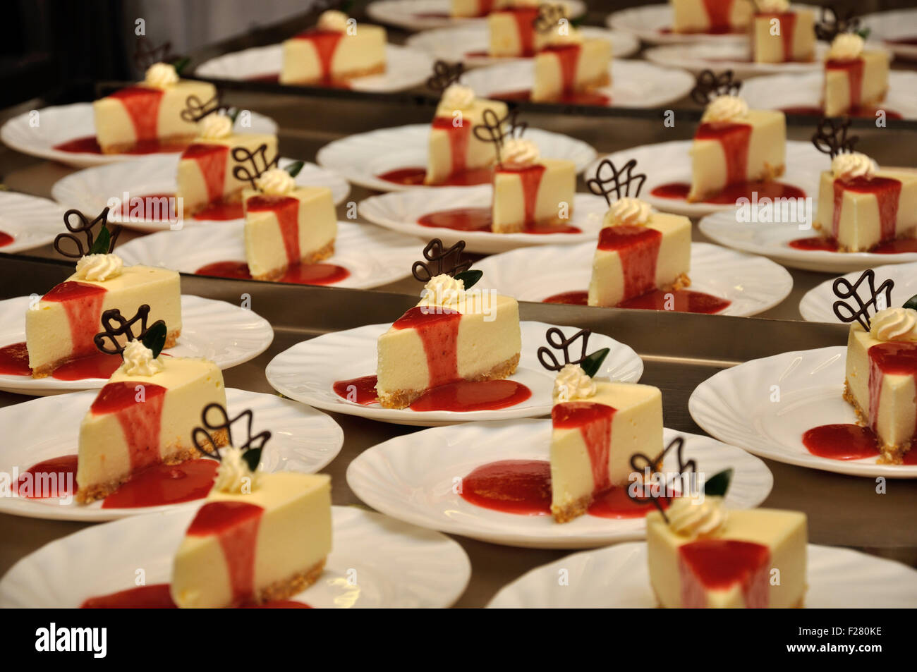 Plates of cheesecake ready to serve at a reception - Stock Image