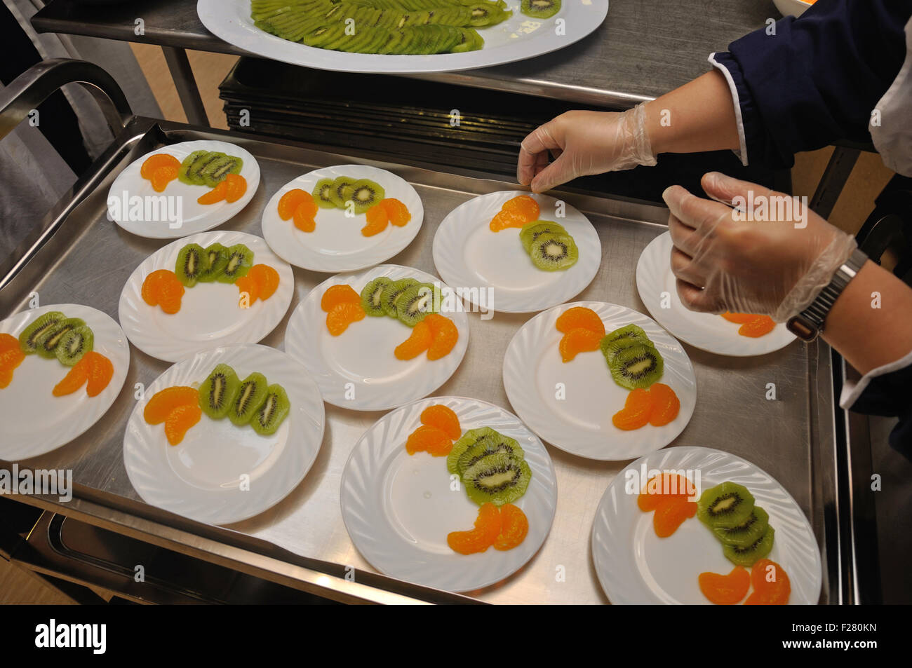 A caterer prepares plates of dessert with slices of kiwi fruit and orange. - Stock Image