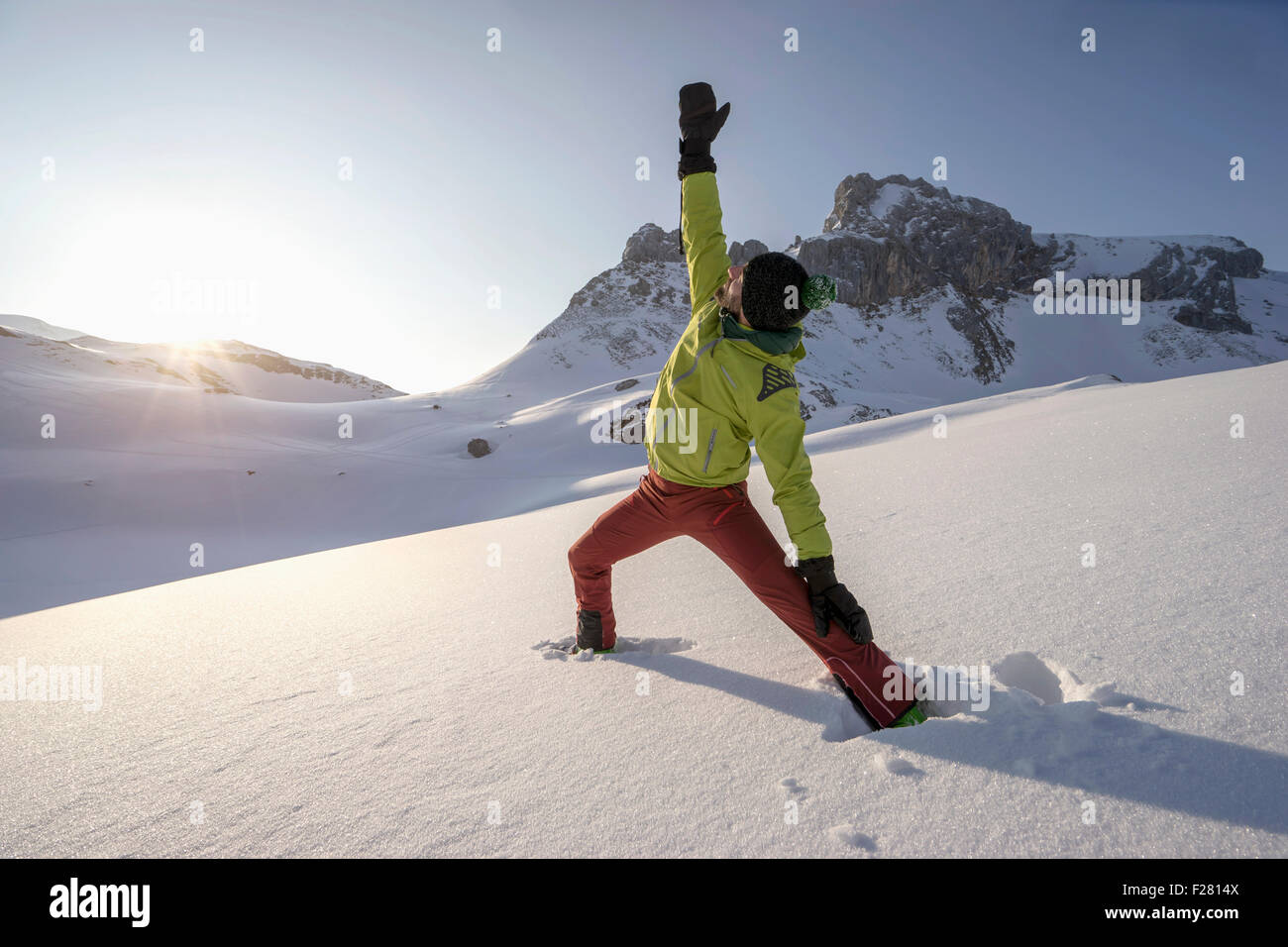 Man doing yoga on snowcapped mountain during sunrise, Tyrol, Austria - Stock Image