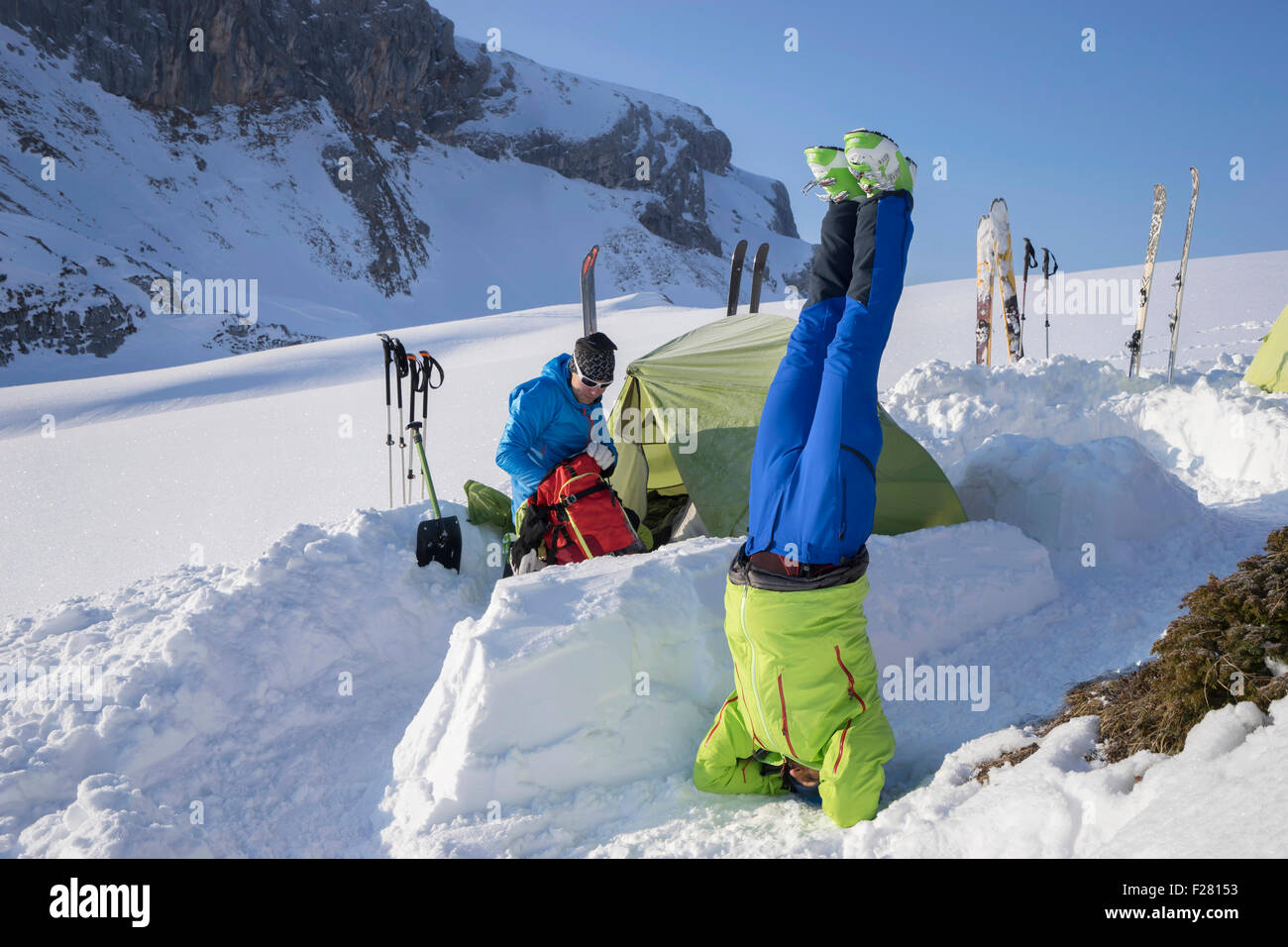 Man doing headstand yoga at camp on snowcapped mountain, Tyrol, Austria - Stock Image