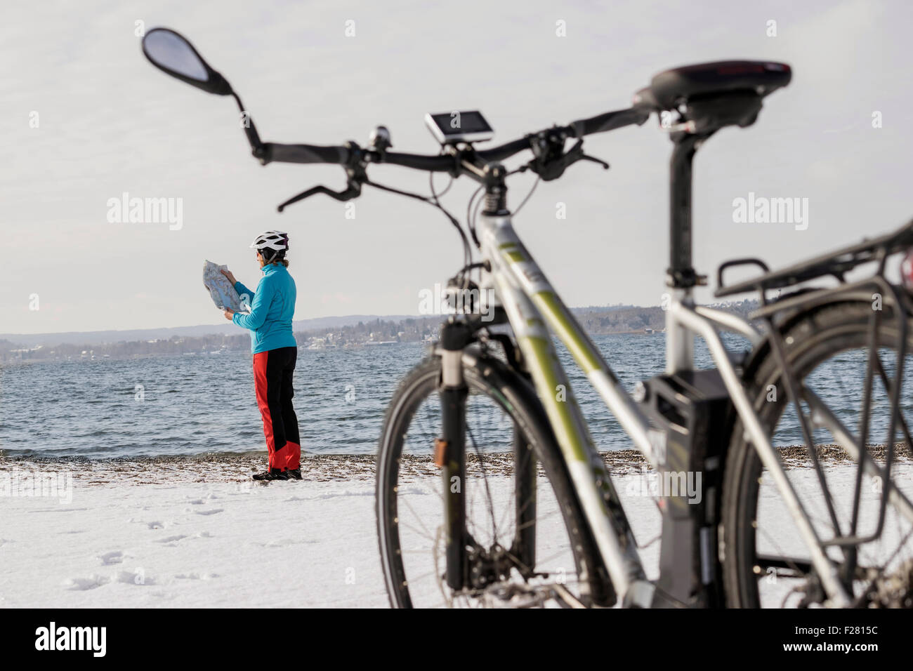 Side profile of mature woman reading map on beach, Bavaria, Germany - Stock Image