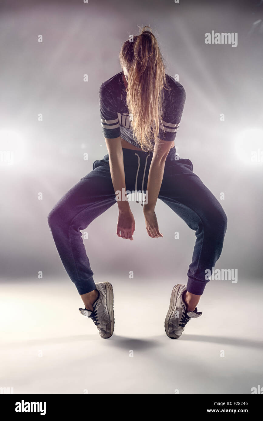 e62b155e3b0f Female Hip Hop Dancer in Tip Toe Position with her Hair Covering her Face  Against Brown