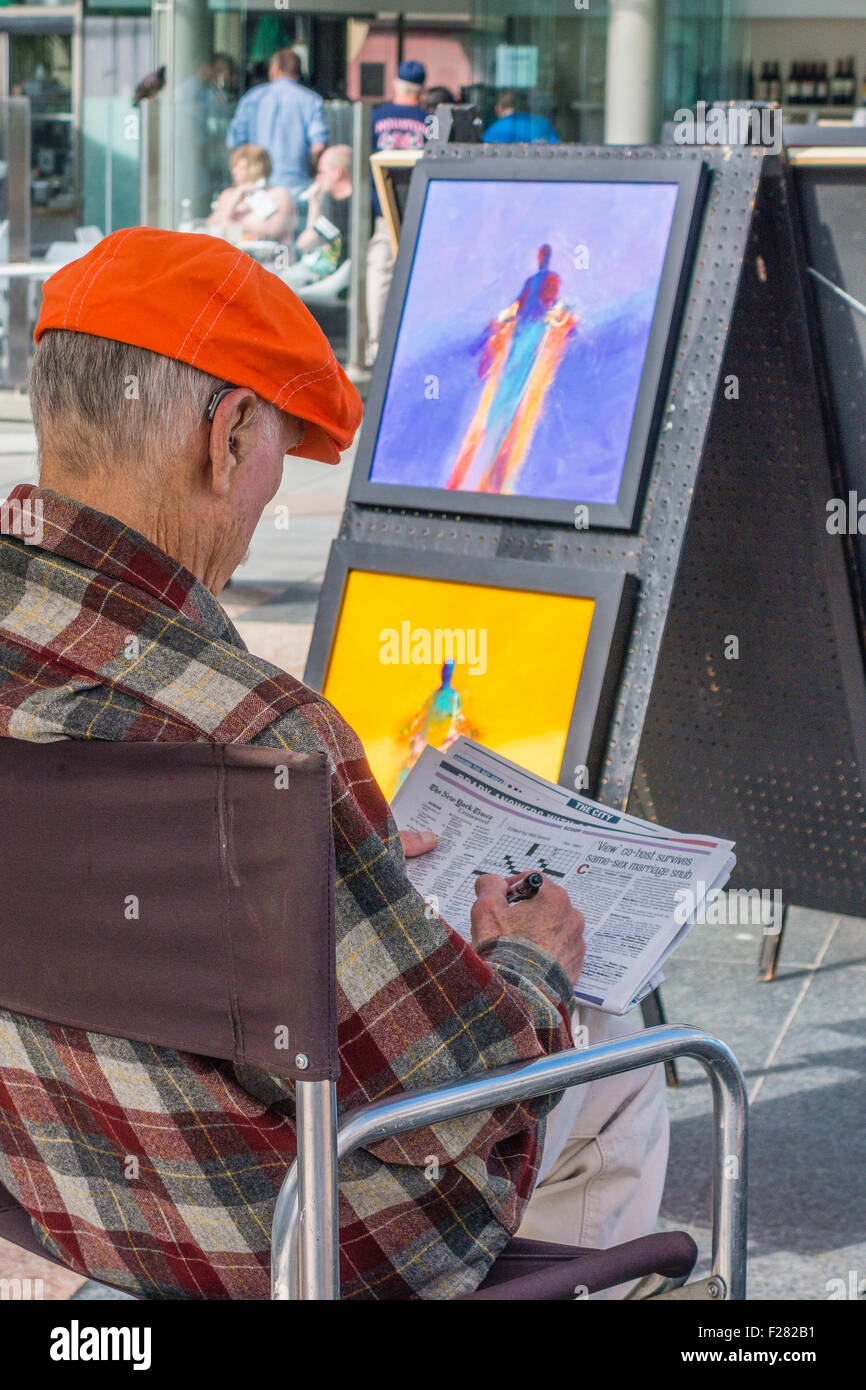 A senior citizen 80-90 year your artist sits and wait for customers as he is displaying paintings in Union Square, - Stock Image