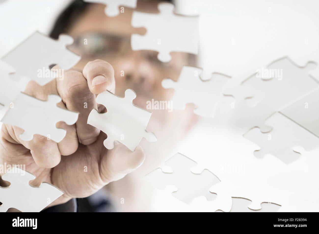 Businessman arranging jigsaw puzzle pieces, Bavaria, Germany - Stock Image