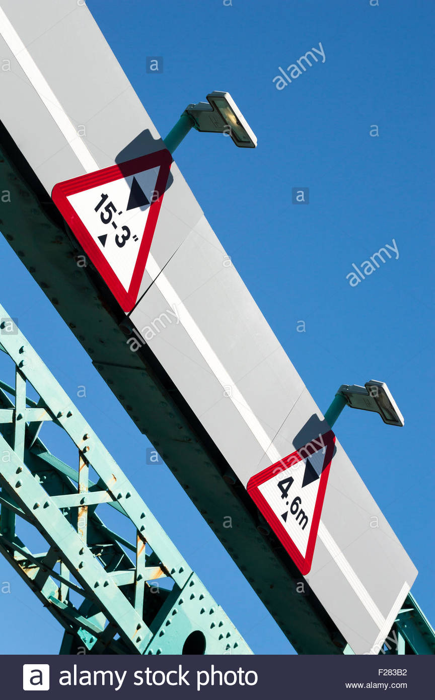 Looking up at imperial and metric height restriction signs above the road on the Twin Sails Bridge, Poole, Dorset, - Stock Image