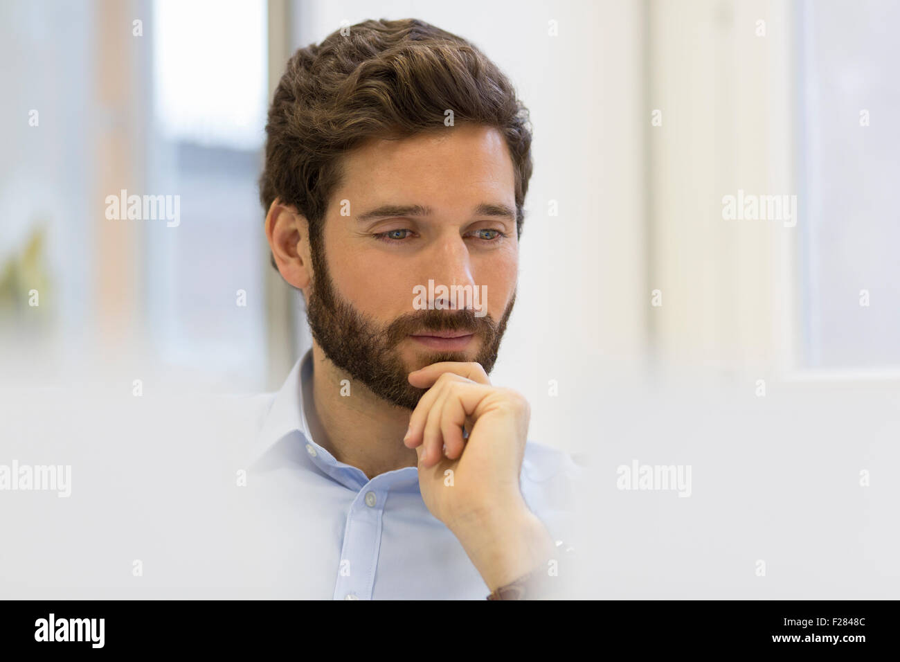 Pensive businessman in modern office - Stock Image