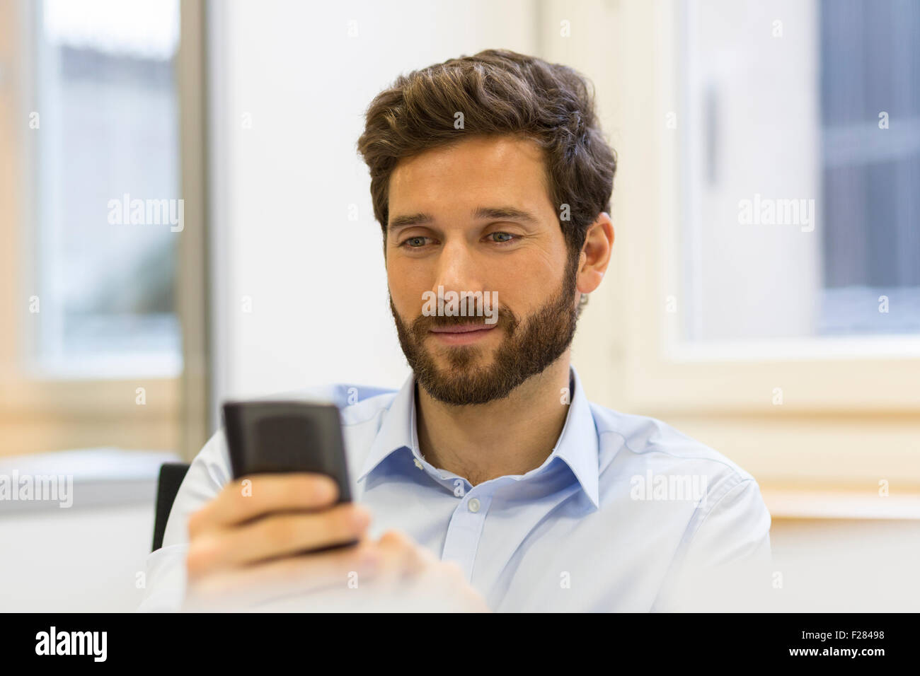 Cheerful bearded man using his smartphone in modern office - Stock Image