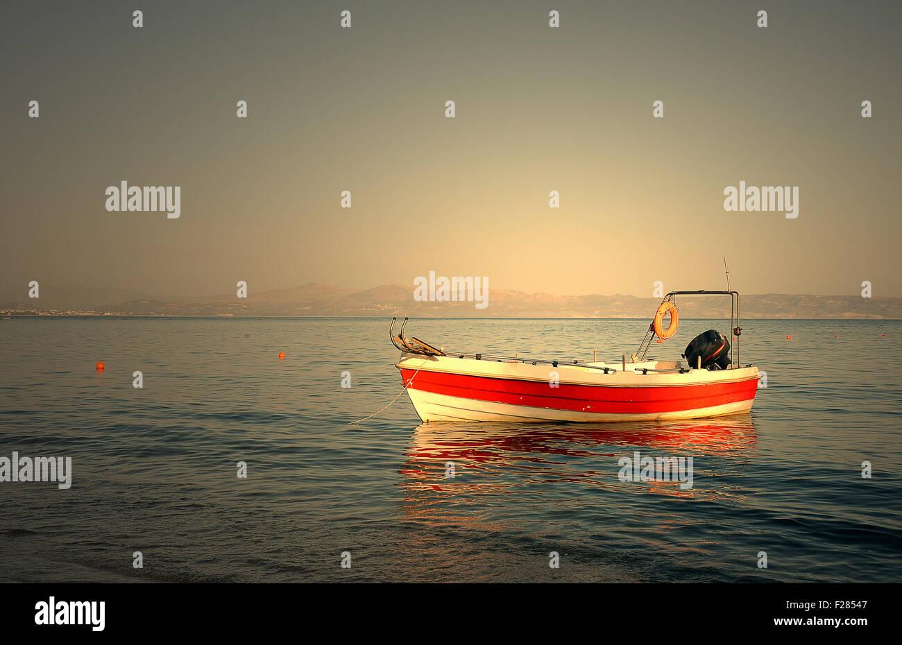 Motorboat anchored in the sea at Agia Galini, Crete, Greece - Stock Image
