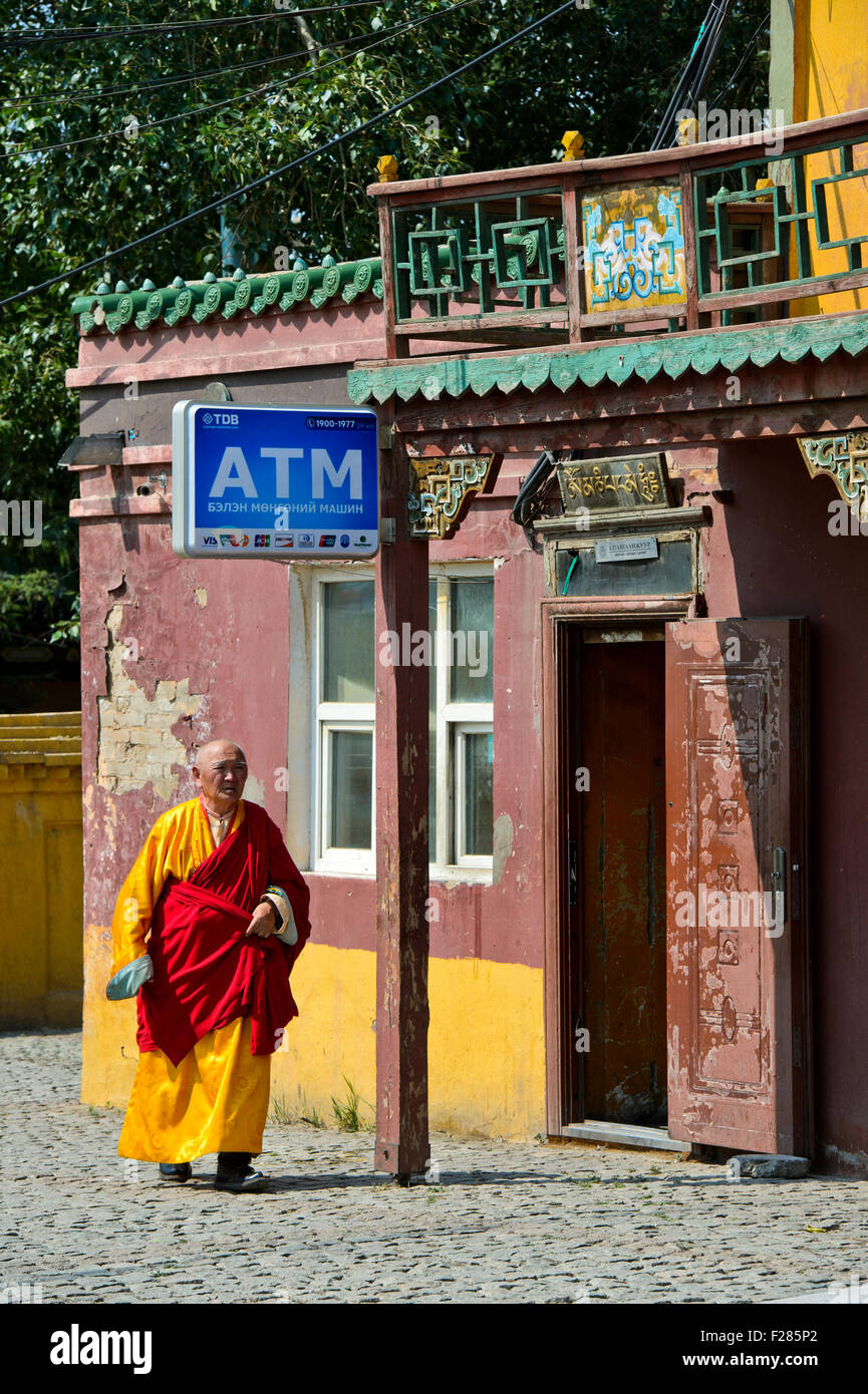 Monk passing by a building for ATMs in the Buddhist Gandan Monastery, Ulaanbaatar, Mongolia - Stock Image