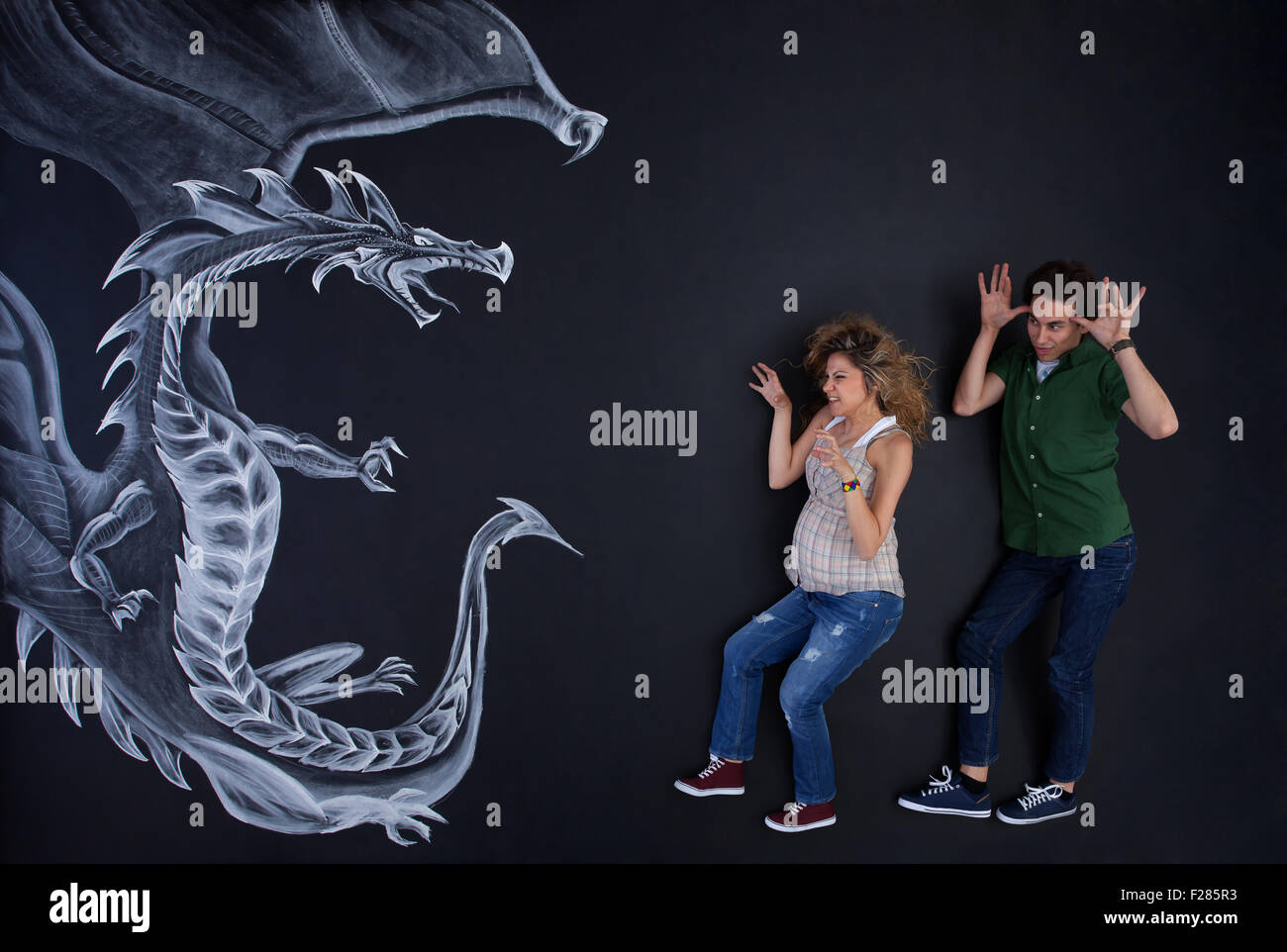 Young couple making fun with a drawing dragon. - Stock Image