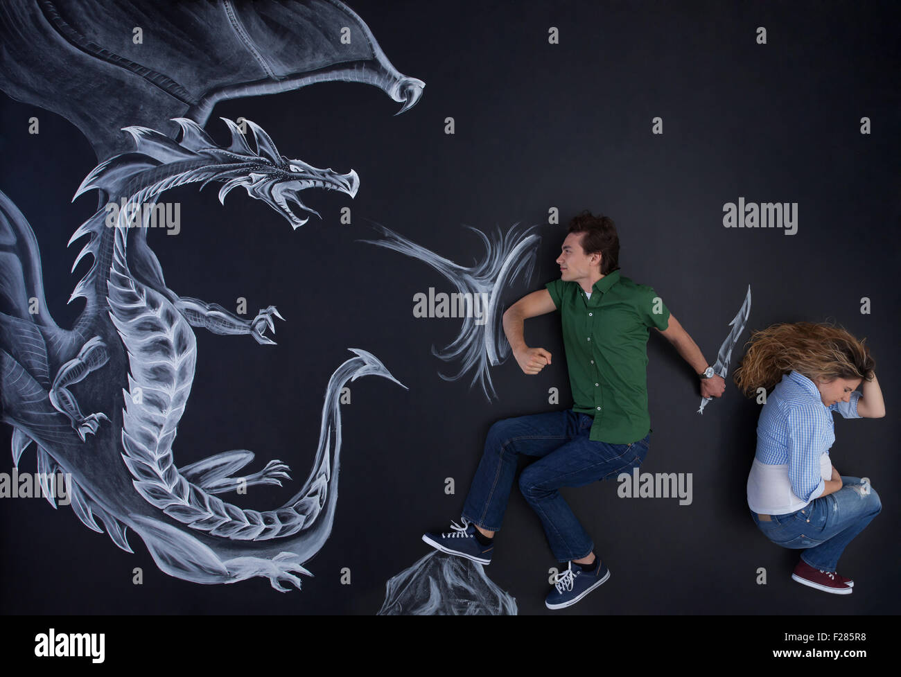 Young man protecting his pregnant woman against a fearless drawing dragon. - Stock Image