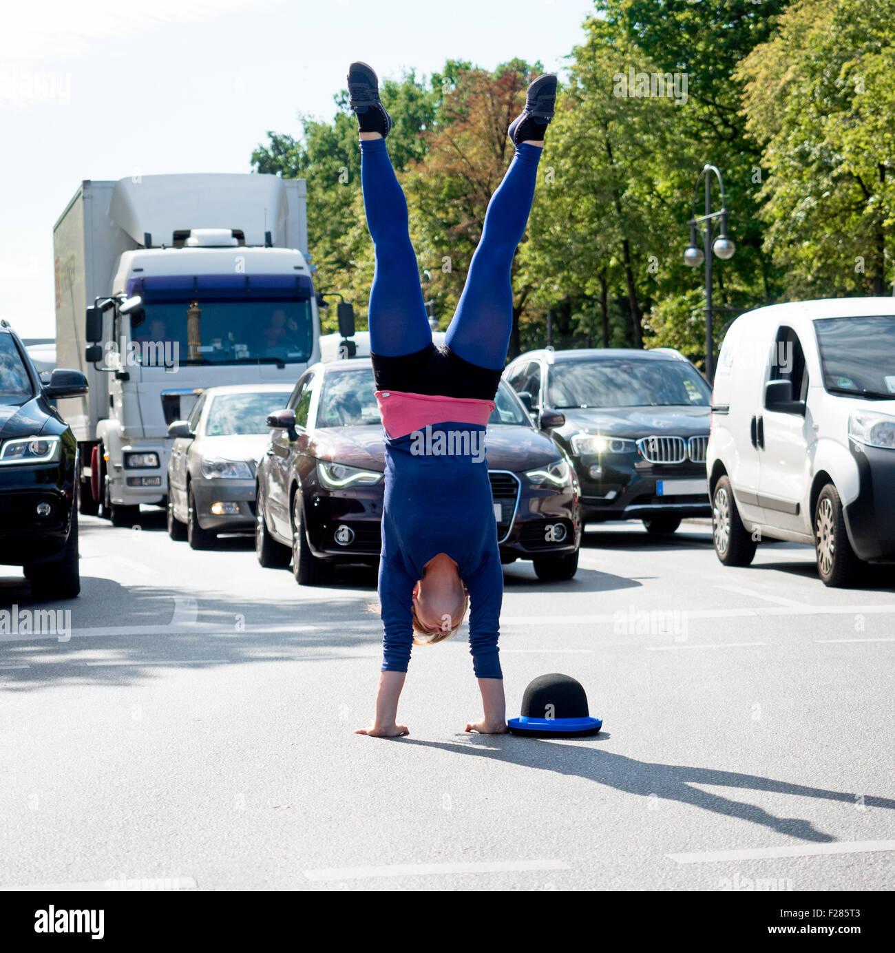 Akrobatin macht Handstand auf der Kreuzung im Autoverkehr - Stock Image