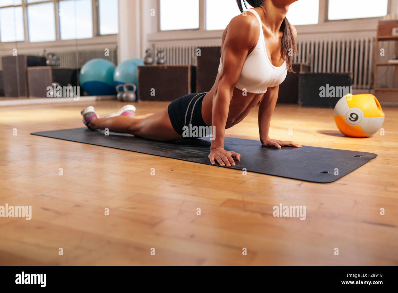 Cropped shot of young woman stretching her stomach on fitness mat. Muscular female doing stretching exercise in - Stock Image