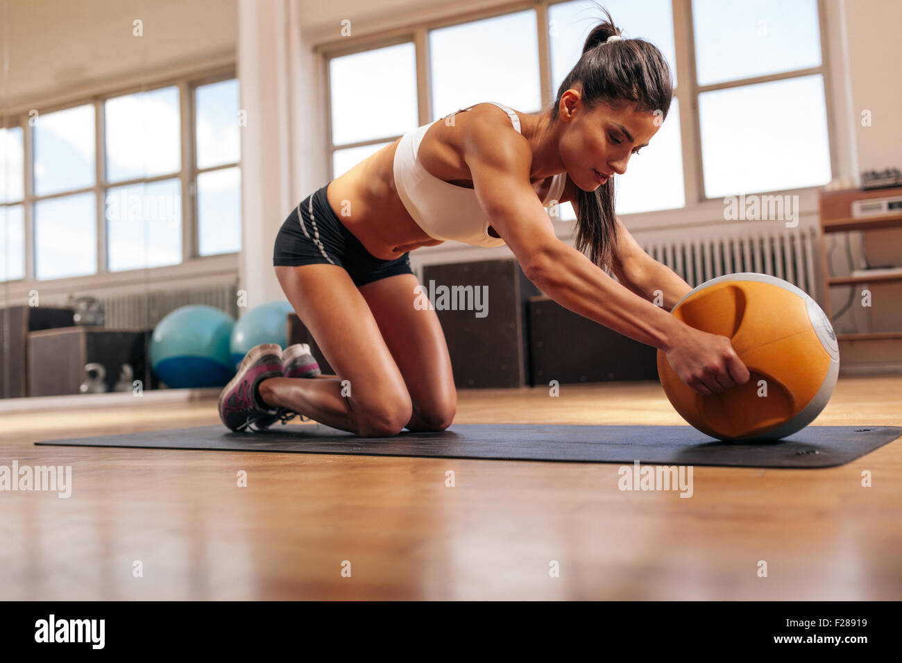Strong young woman doing intense workout with kettlebell in gym. Young muscular woman doing core exercise on fitness - Stock Image