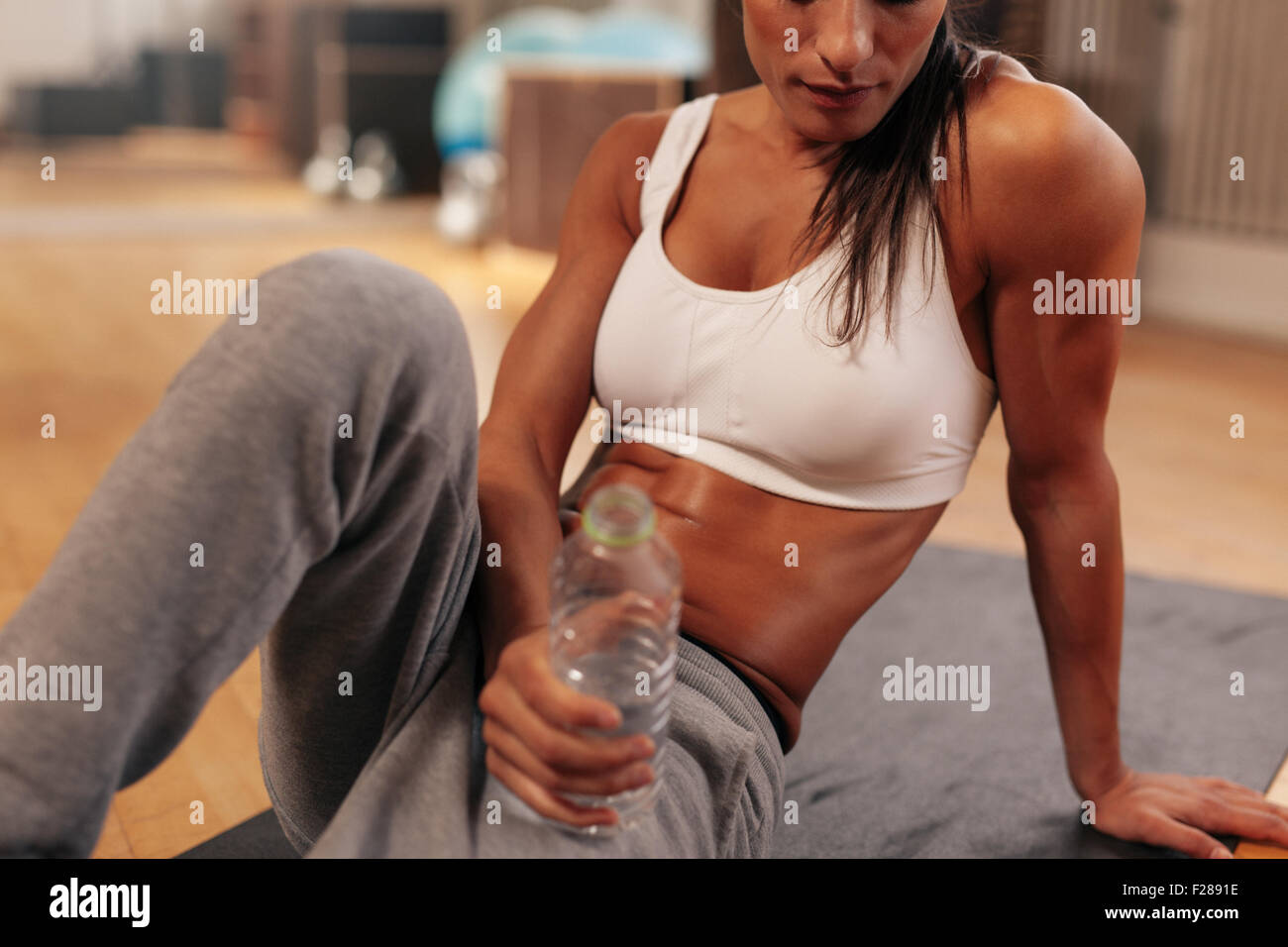 Cropped shot of fitness woman holding water bottle at gym. Focus on water bottle. Female sitting on exercise mat. - Stock Image