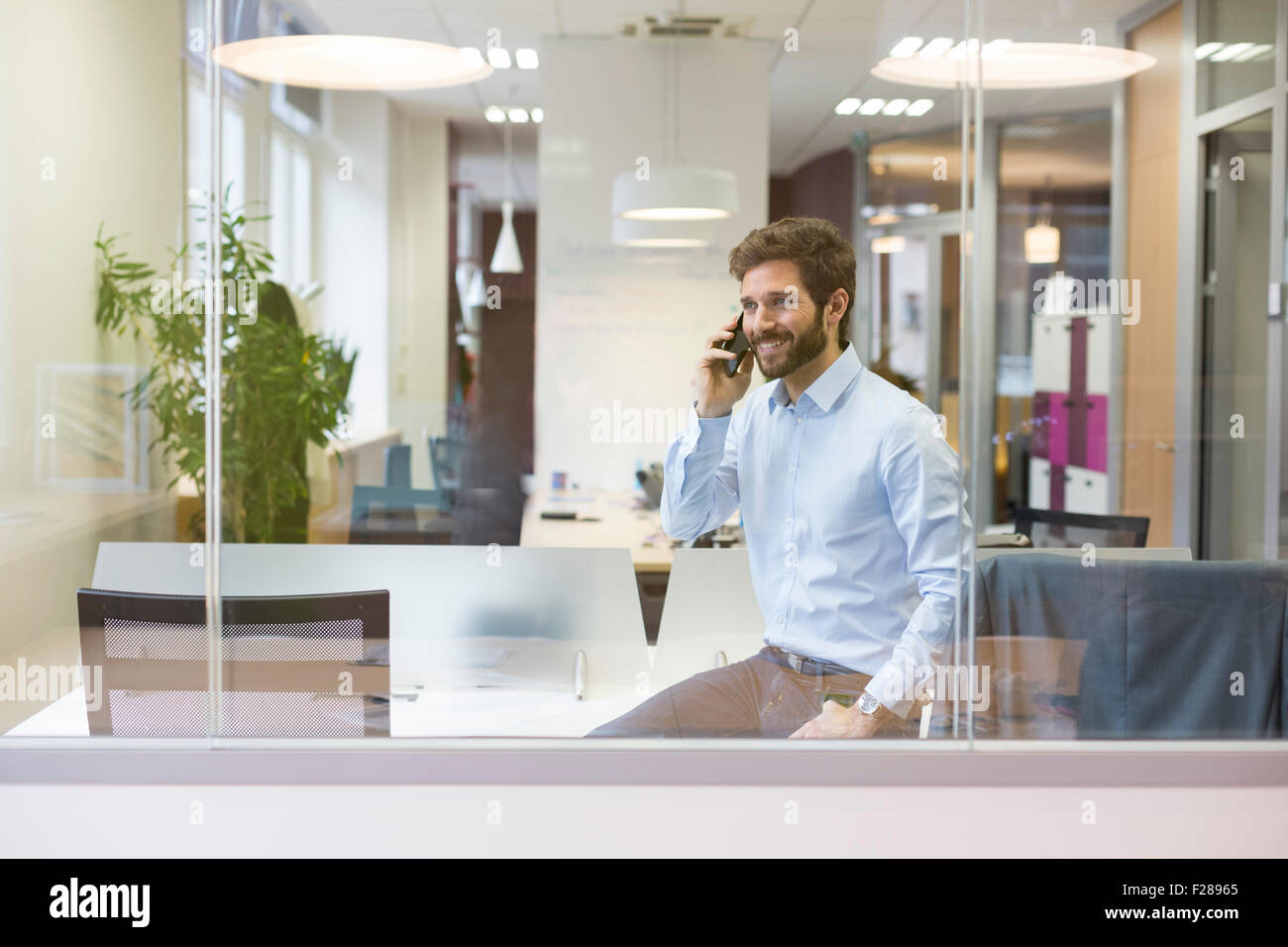One casual businessman on the mobile phone in open space office - Stock Image