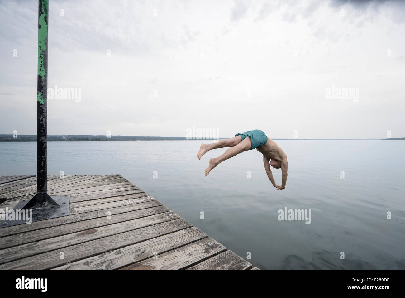 Mature man jumping into water on pier, Baden-Wurttemberg, Bavaria, Germany - Stock Image